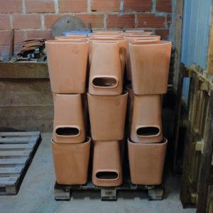 Empilement de pots composteurs en terre cuite dans l'atelier de la poterie d'Amance