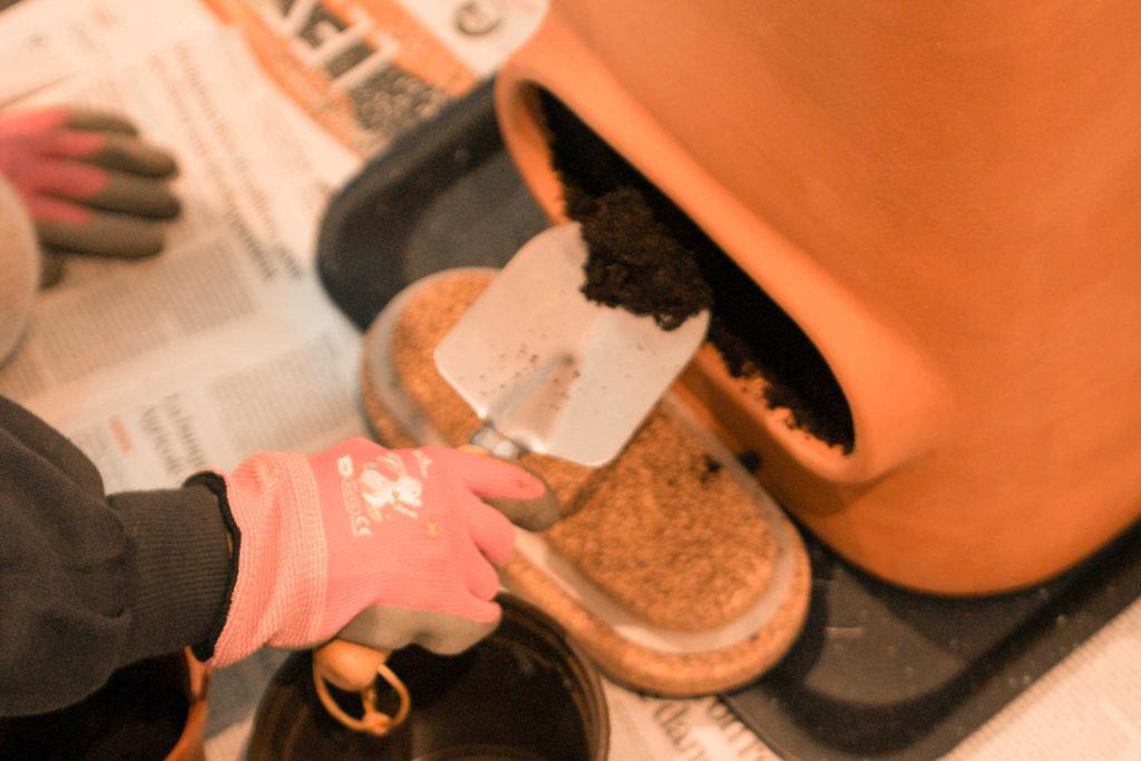 récolte du compost dans l'ouverture inférieure du potde fleurs composteur avec une petite pelle de jardin
