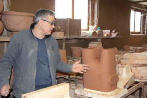 Etienne Drouilly céramiste dans son atelier des Poteries d'Amance avec le pot de fleurs composteur