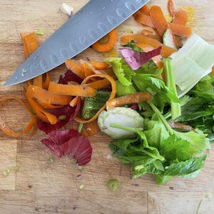 épluchures carottes, fenouil, céleri, oignon rouge, couteau de cuisine sur planche à découper en bois