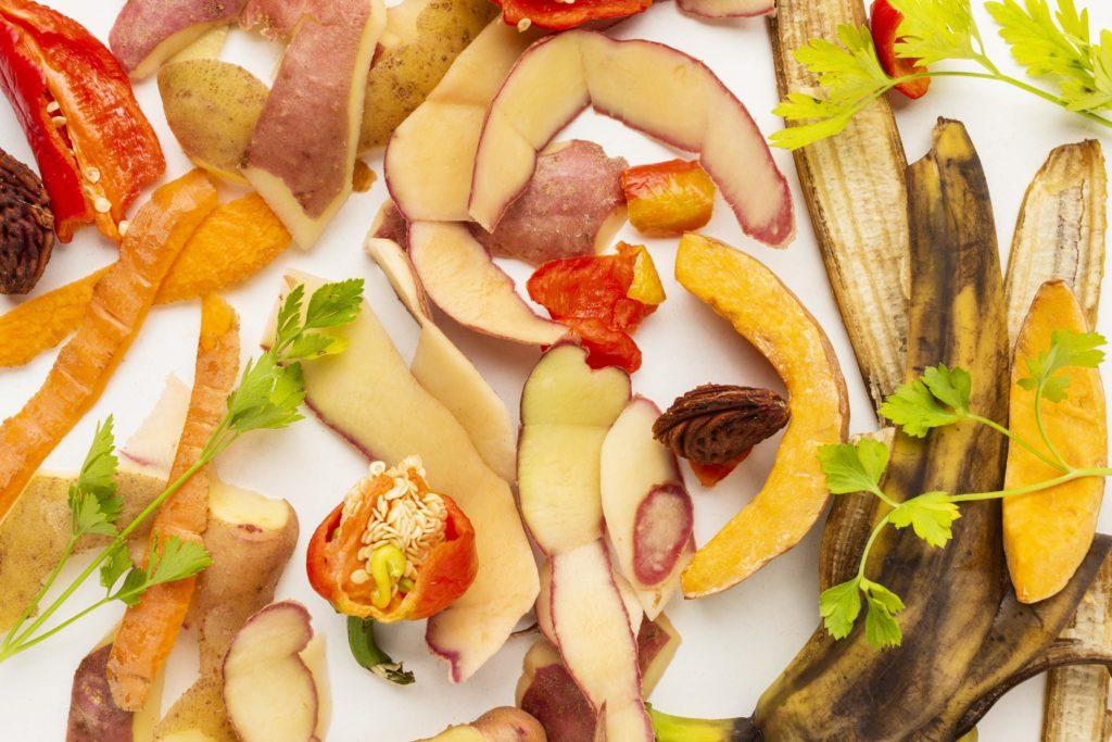 composition visuelles de biodéchets sur fond blanc : poivrons, épluchures de pomme et carotte, pomme de terre persil, peau de banane