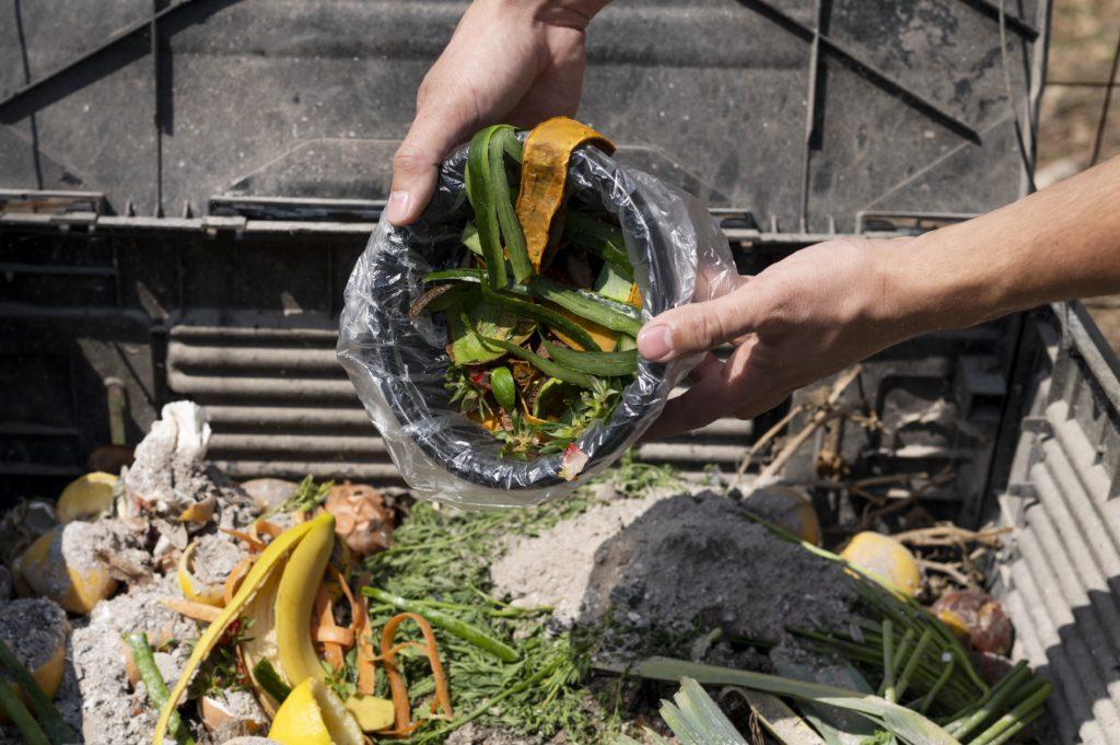 personne jetant ses biodéchets dans un composteur extérieur